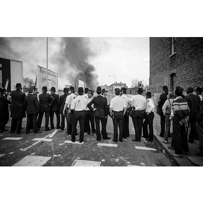 Poorly equipped and ill-prepared police officers look toward the centre of rioting at the far end of Railton Rd.