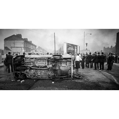 Police gather at the fork of Railton rd and Mayall Rd behind a burnt out police vehicle. Brixton, April 1981
